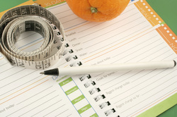 Food journaling health and wellness blog - journal with measuring tape and orange